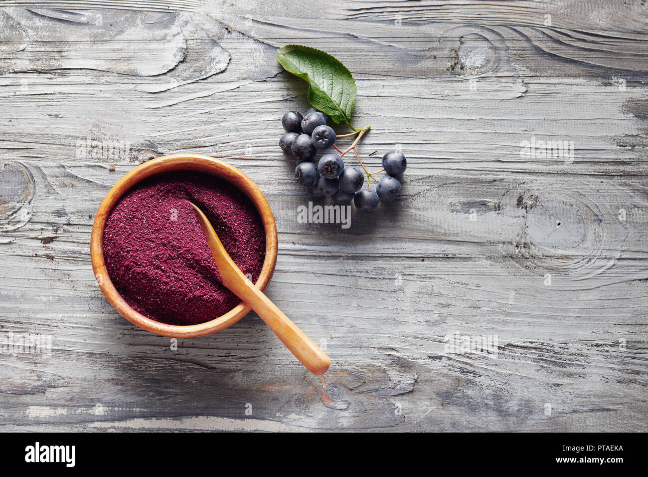 Organic Aronia powder in a bowl with fresh aronia berries on table. - Stock Image