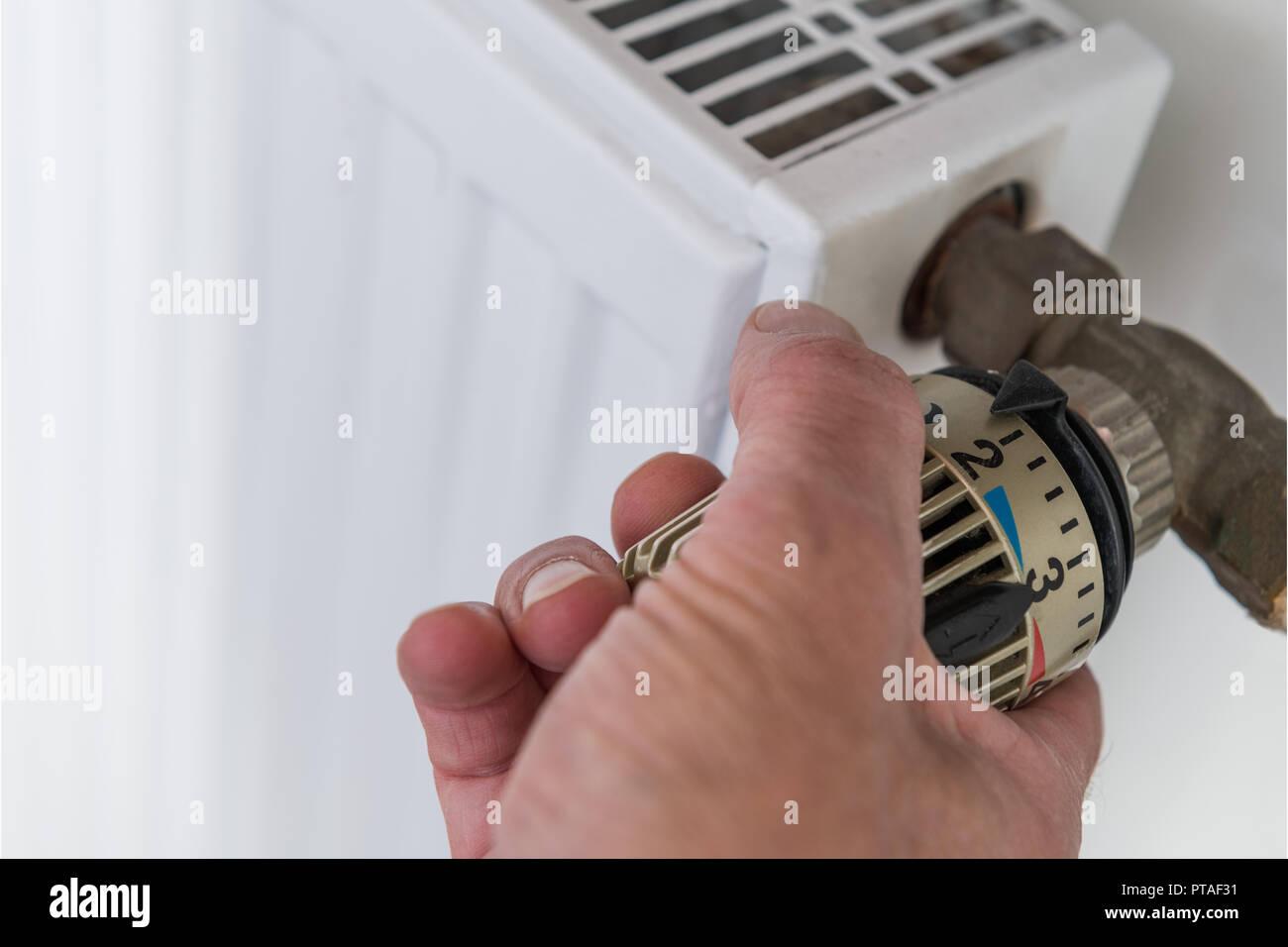 Hand on heater thermostat Stock Photo