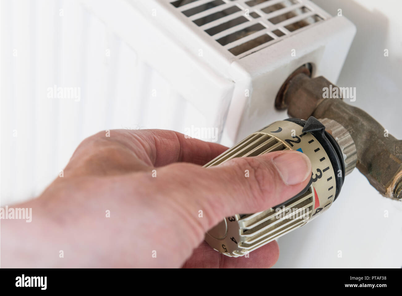 Hand on heater thermostat Stock Photo