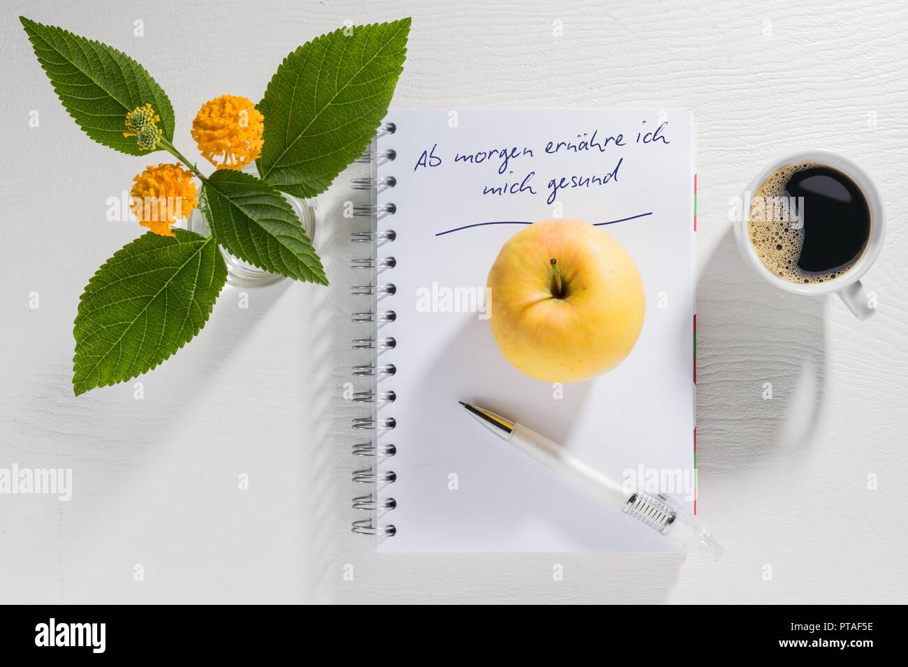 Writing pad with New Year's resolution with coffee cup and flowers on a white table Stock Photo