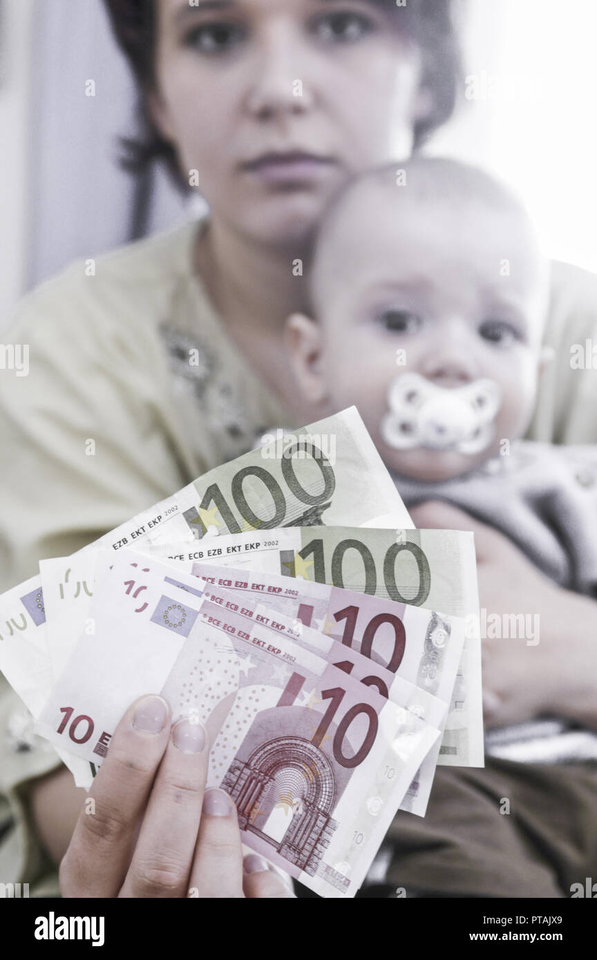 Young mother with baby, counting the housekeeping, child allowance, alimonies (model-released) - Stock Image