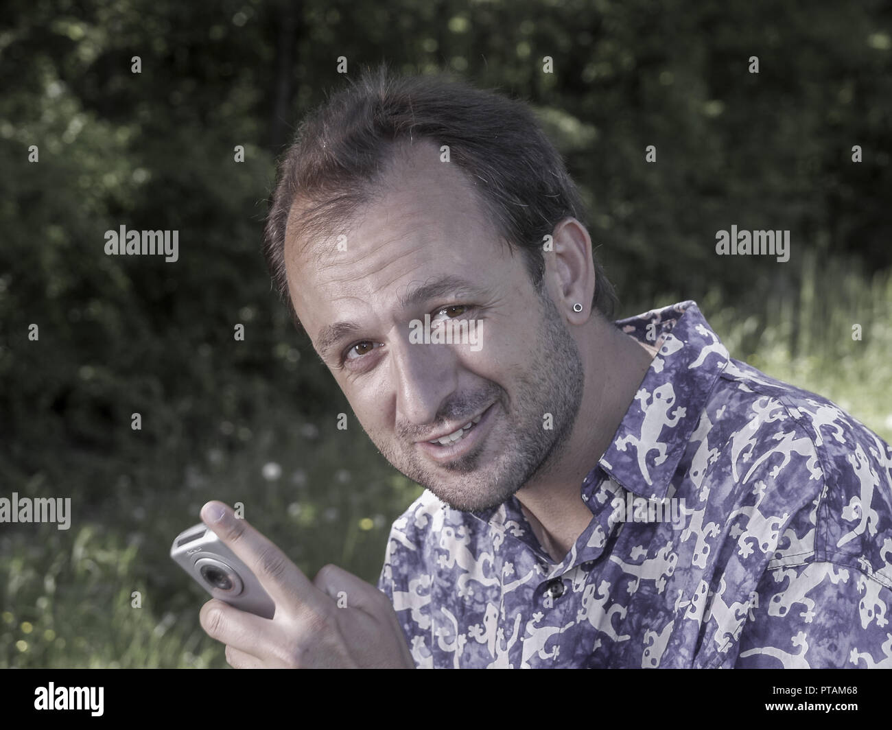 Man with blue shirt and mobile phone outdoors (model-released) Stock Photo