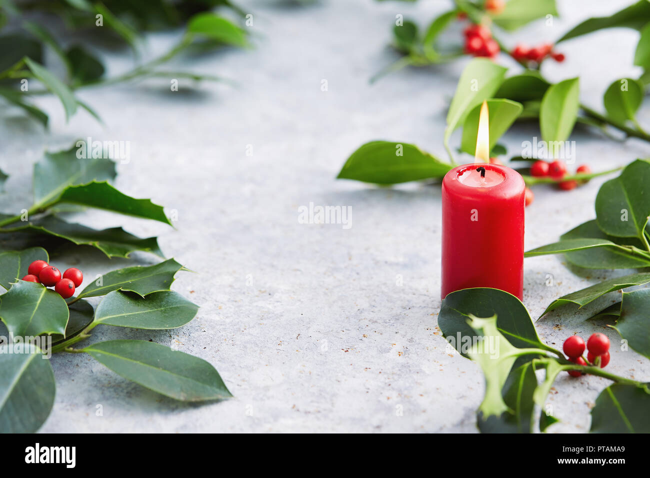 christmas decorations candle with evergreen decorations holly leaves with red berries
