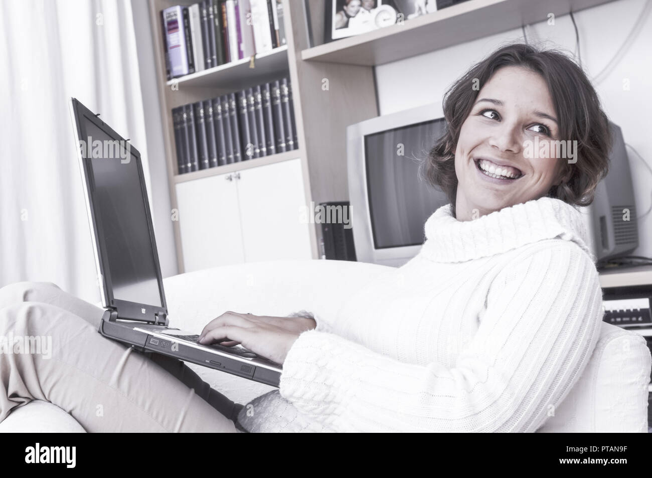 Young woman with laptop in living room (model-released) Stock Photo