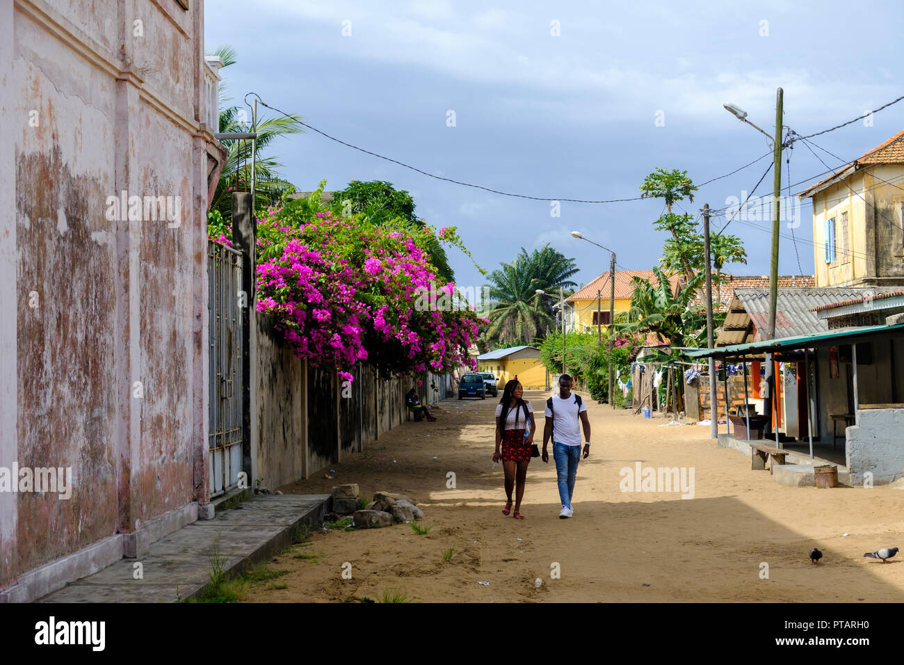 GRAND BASSAM, COTE DIVOIRE – APRIL 9 2018: Young couple stroll through bougainvillea lined street in old colonial district of former capital of Ivory  - Stock Image