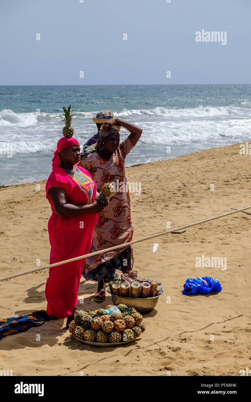 GRAND BASSAM, COTE DIVOIRE – APRIL 9 2018: Woman in bright pink dress balances a pineapple on her head as she prepares fruit for selling alongside nut - Stock Image