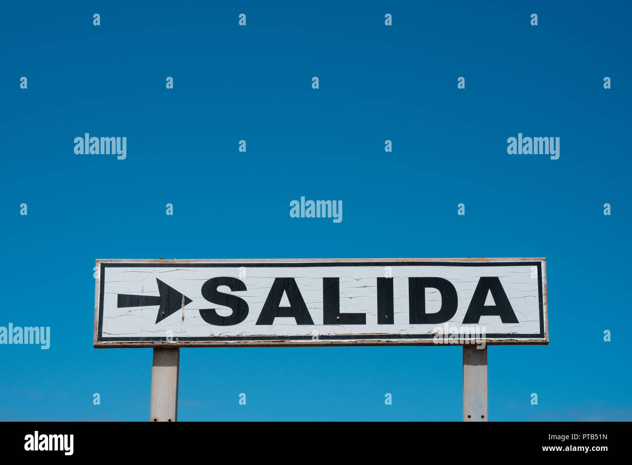 Exit sign (spanish: SALIDA) isolated on blue sky - Stock Image