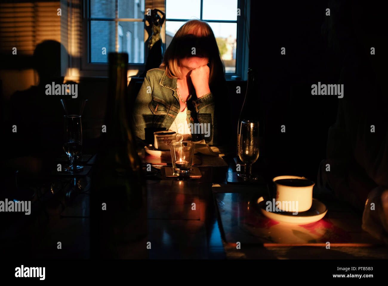 Mature woman in shadow with arms on table after eating a meal - Stock Image