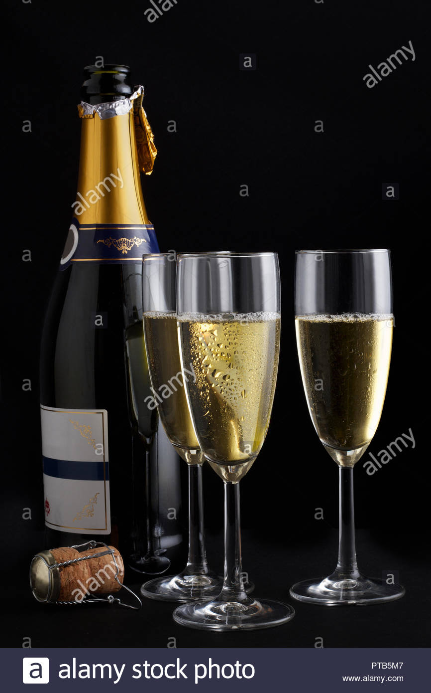 Glasses filled with champagne in front of a bottle - Stock Image