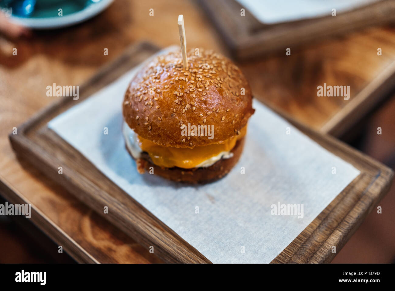 Close up of fresh juicy burger on wooden cutting board in cafe. - Stock Image