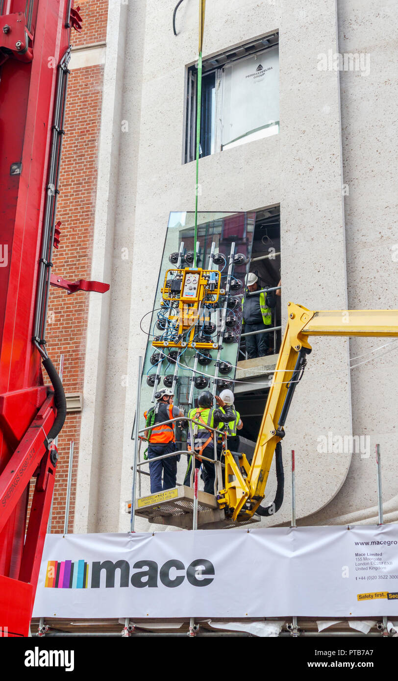 Building contractor Mace workers on a cherry picker hoist carefully fitting a large new glass window pane into a building in Mayfair, London, UK - Stock Image
