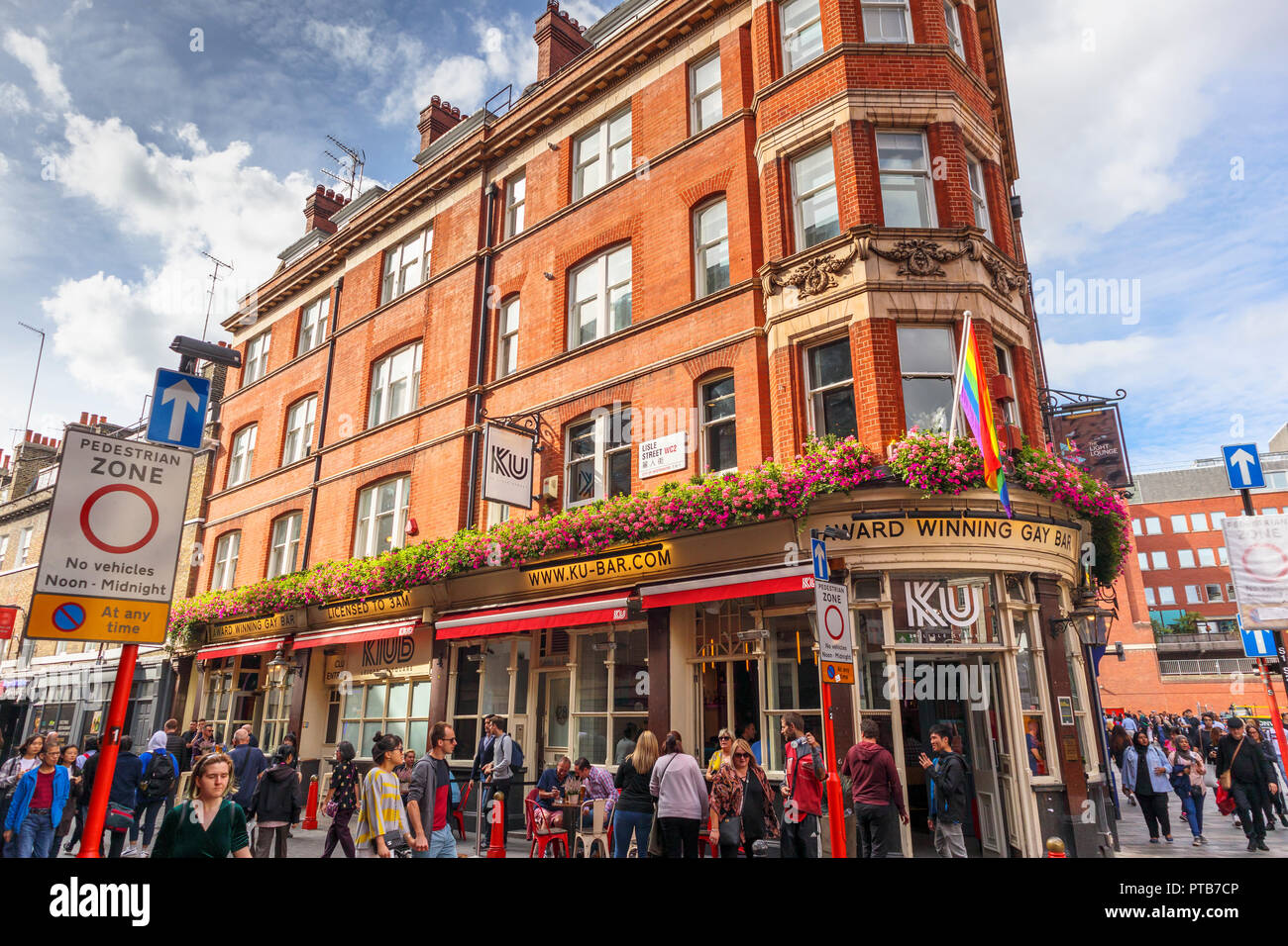 Ku Bar, a popular and famous gay bar in Lisle Street, on a busy crowded afternoon in Chinatown in Soho, City of Westminster, West End of London, UK - Stock Image