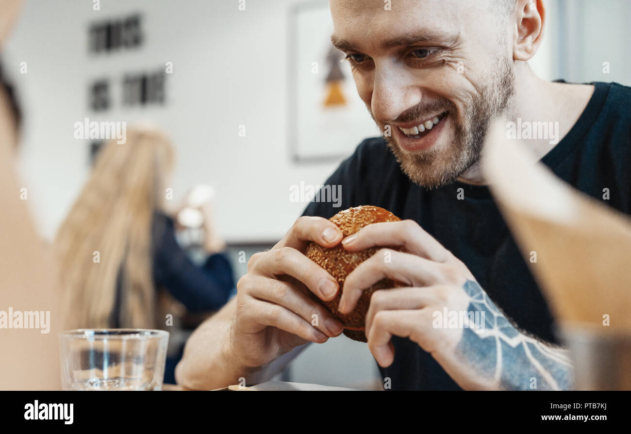 Close up of young handsome man eating fresh juicy burger at cafe and smiling. - Stock Image