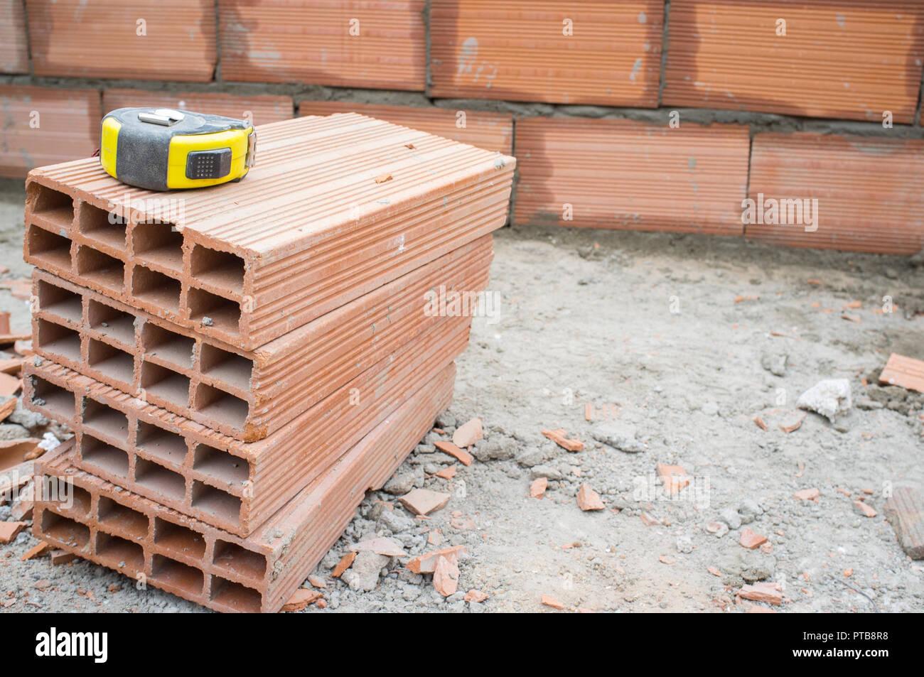 Measuring tape over clay-based bricks. Closeup - Stock Image