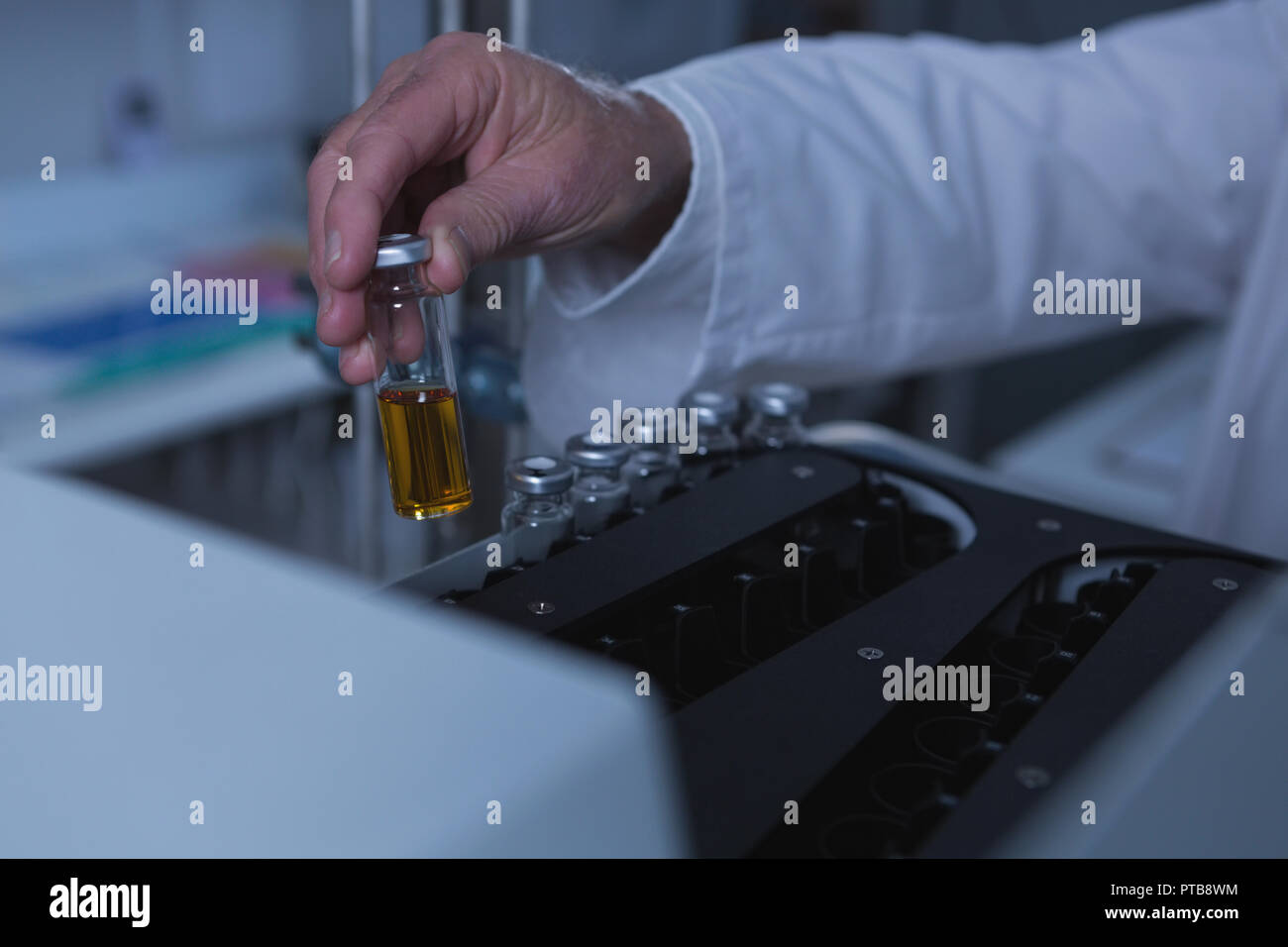 Male scientist placing chemical bottle on a machine 4k - Stock Image