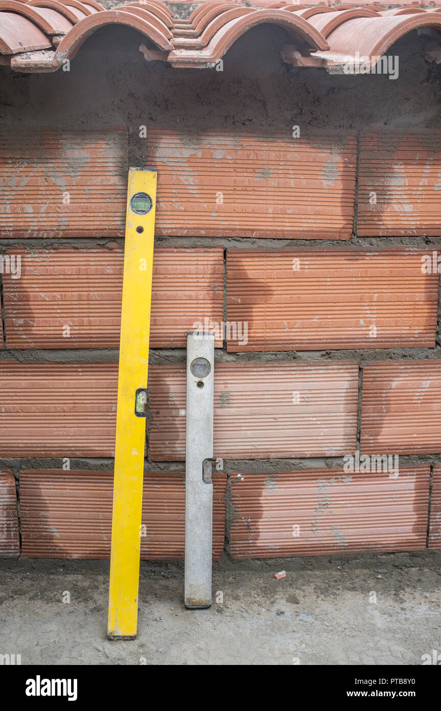 Spirit levels over recently made brick wall - Stock Image