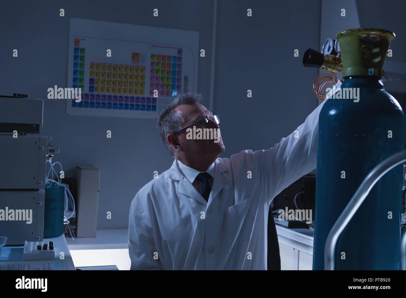 Male scientist adjusting pressure gauge of cylinder - Stock Image