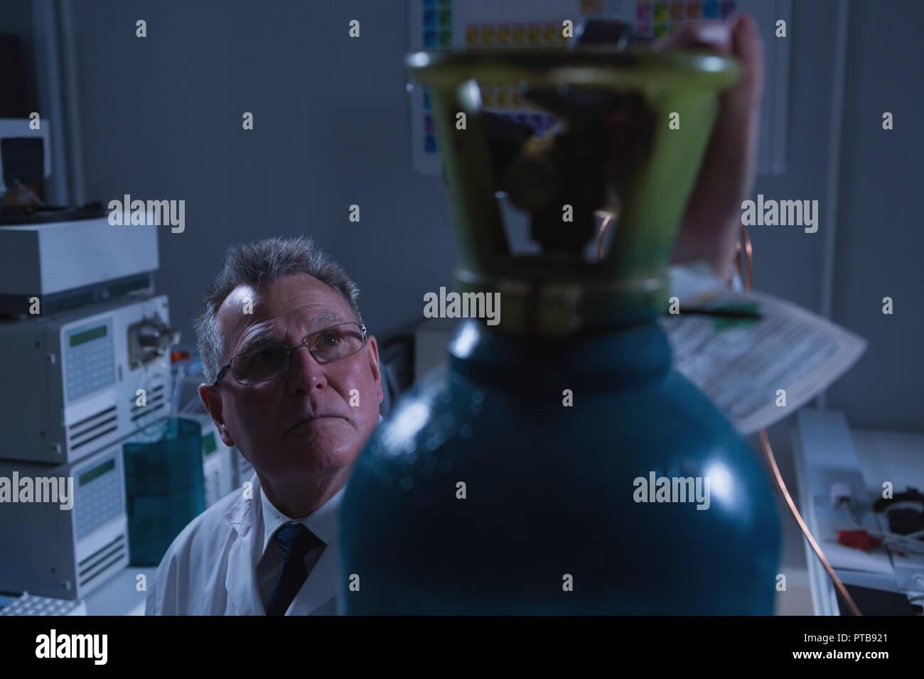 Male scientist adjusting pressure gauge of cylinder in laboratory - Stock Image