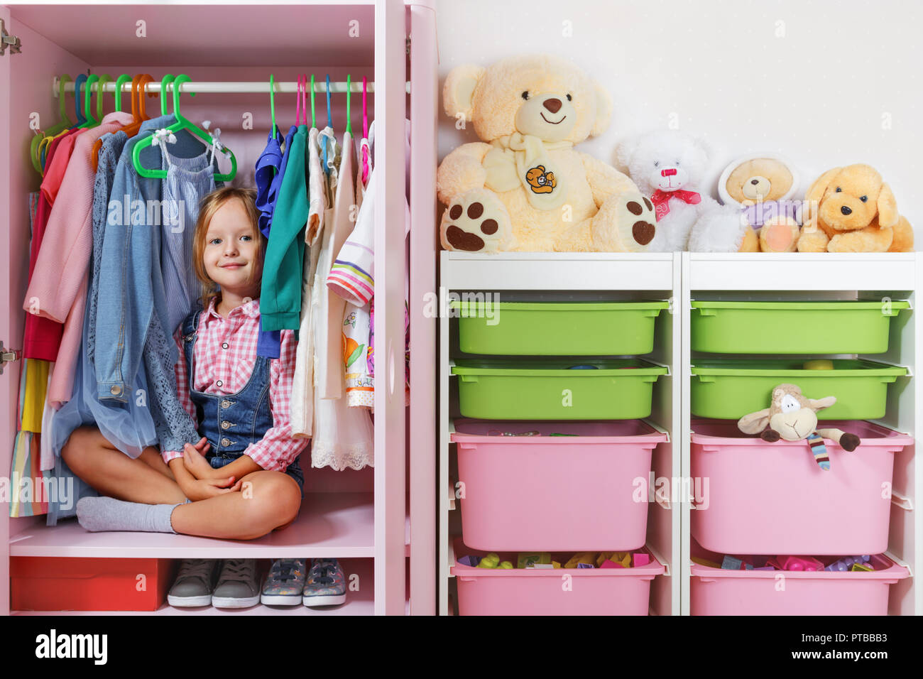 A little child girl is sitting in a wardrobe in a children's room. Saving and storage system for children's things and toys concept. Stock Photo