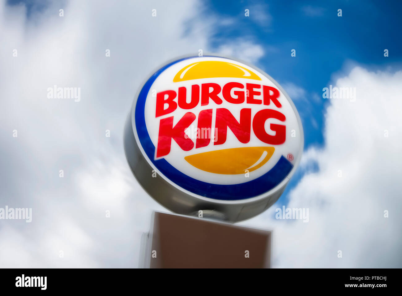 Advertising sign a Burger King branch in front of cloudy skies - Stock Image