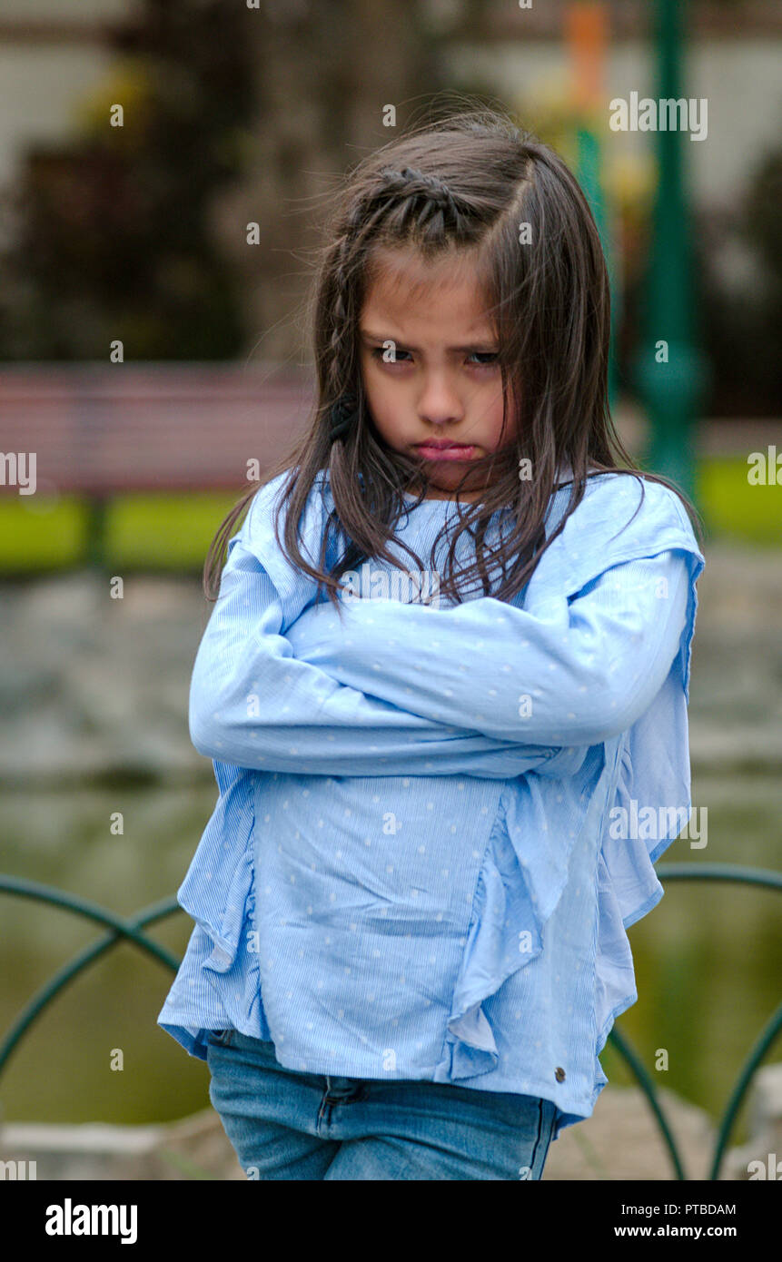 Angry little girl showing frustration and disagreement in the street - Stock Image