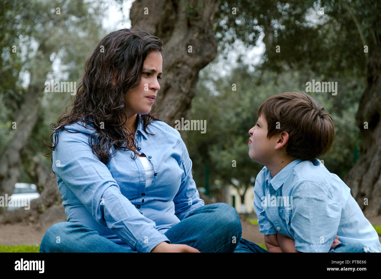 Portrait of a mother scolding to her baby daughter sitting on the floor in the living room at homePortrait of a mother scolding to her son sitting on the grass in the park. - Stock Image
