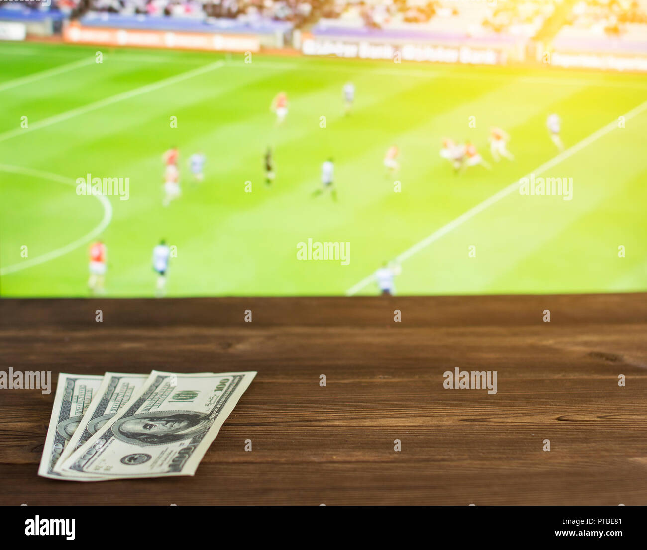 Money dollars on the background of the TV on which show Gaelic football, sports betting, dollars, Gaelic Football Stock Photo