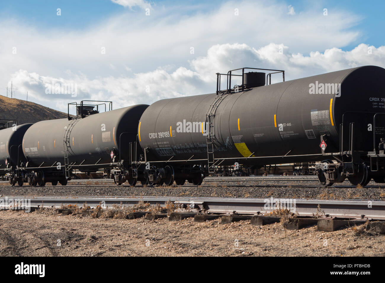 Railroad tank cars carrying hazardous materials on a siding in a train yard. - Stock Image