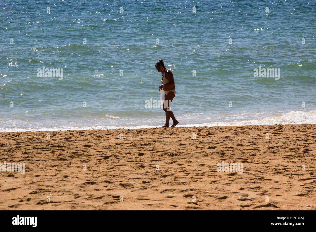 28 September 2018 A solitary female in a Bikini gathering shells and stones on a sandy Praia do inatel beach Albuferia in the Algave Portugal - Stock Image