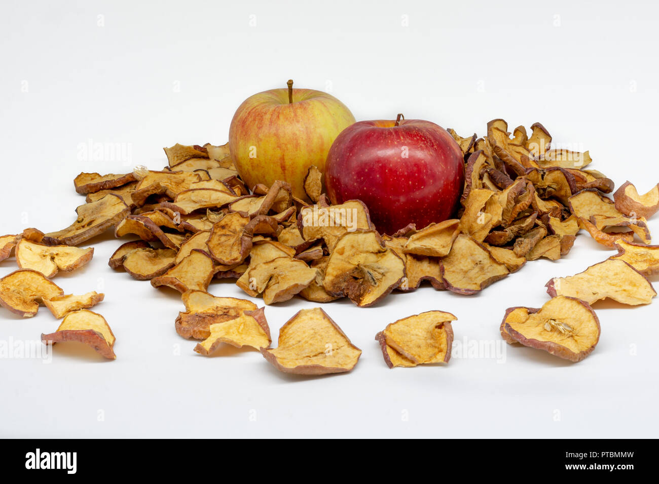 Two apples, one yellow and the other red, surrounded by many slices of dehydrated apple slices with a clean and light white background - Stock Image