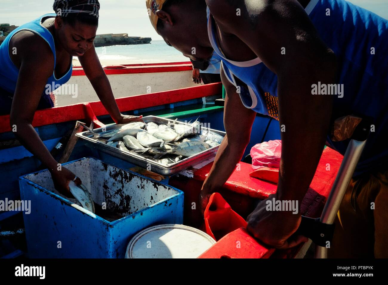 Vila do Maio ,Maio Island, Cape Verde - Jan 5 2016: local fisherman offloading his catch while the woman from the market is going forward to check his - Stock Image