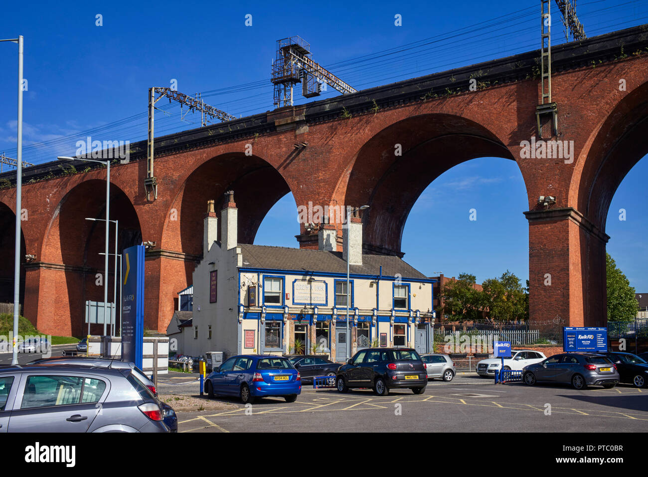 Crown Inn dwarfted and underneath the vast brick built railway viaduct at Stockport - Stock Image