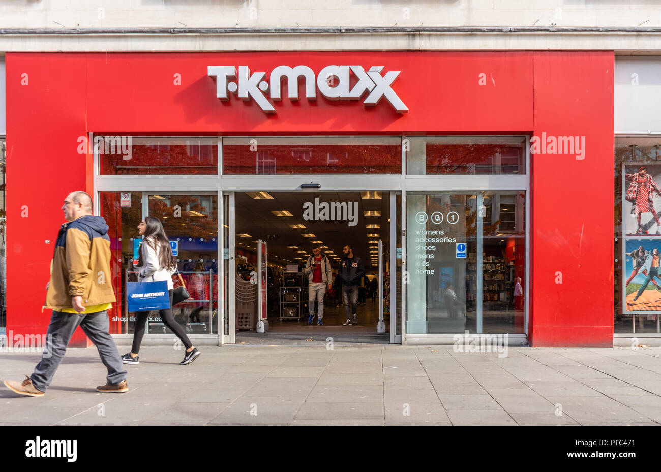66f619d649780 A woman walking past a TK MAXX store front in Southern England, UK, Europe