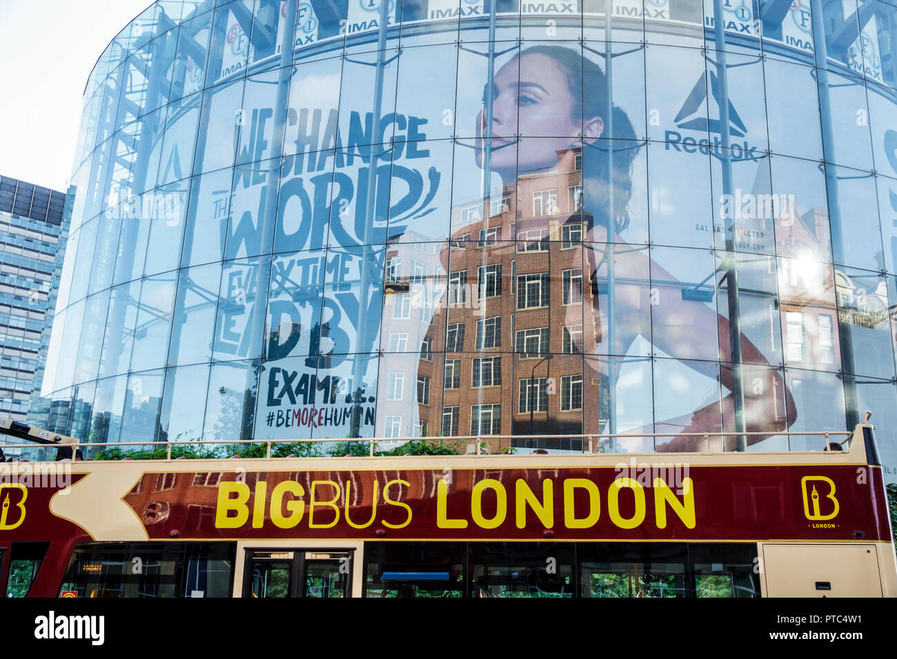 London England United Kingdom Great Britain Lambeth South Bank BFI IMAX cinema Movie theater theatre building exterior glass reflection big bus hop-on - Stock Image