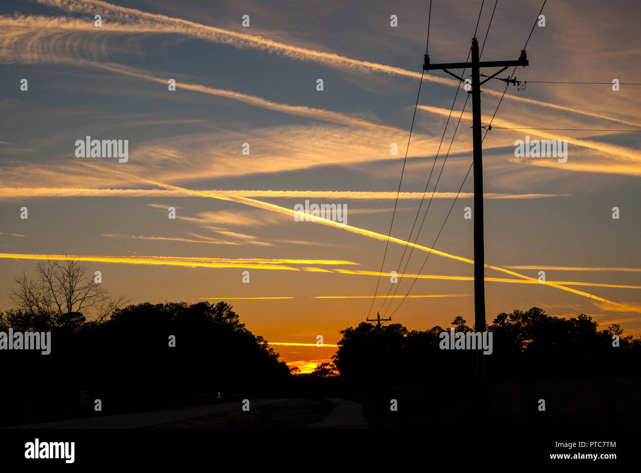 Jet contrails crisscross the skies at sunset in North Central Florida. Stock Photo