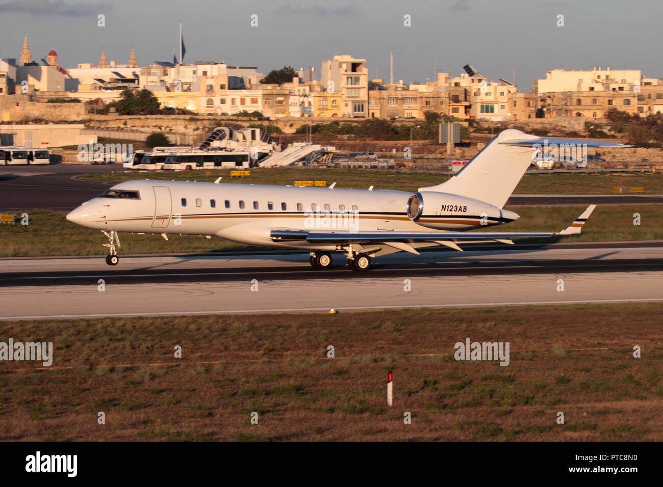Bombardier Global Express large business jet aeroplane keeping its nose up while landing in Malta at sunset - Stock Image