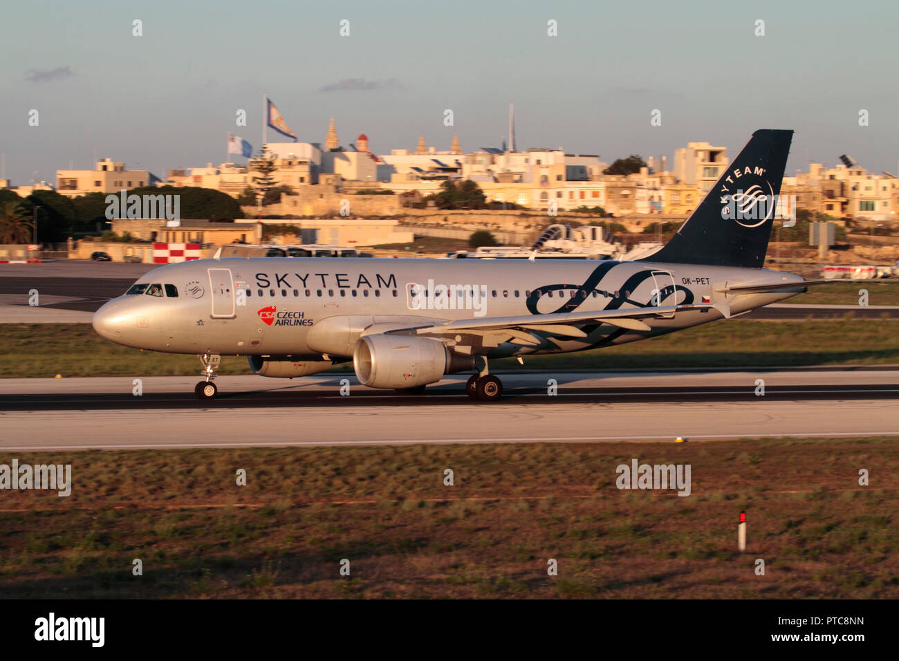 CSA Czech Airlines Airbus A319 passenger jet plane in the colours of the Skyteam airline alliance taking off from Malta at sunset. Intra-EU flights. - Stock Image