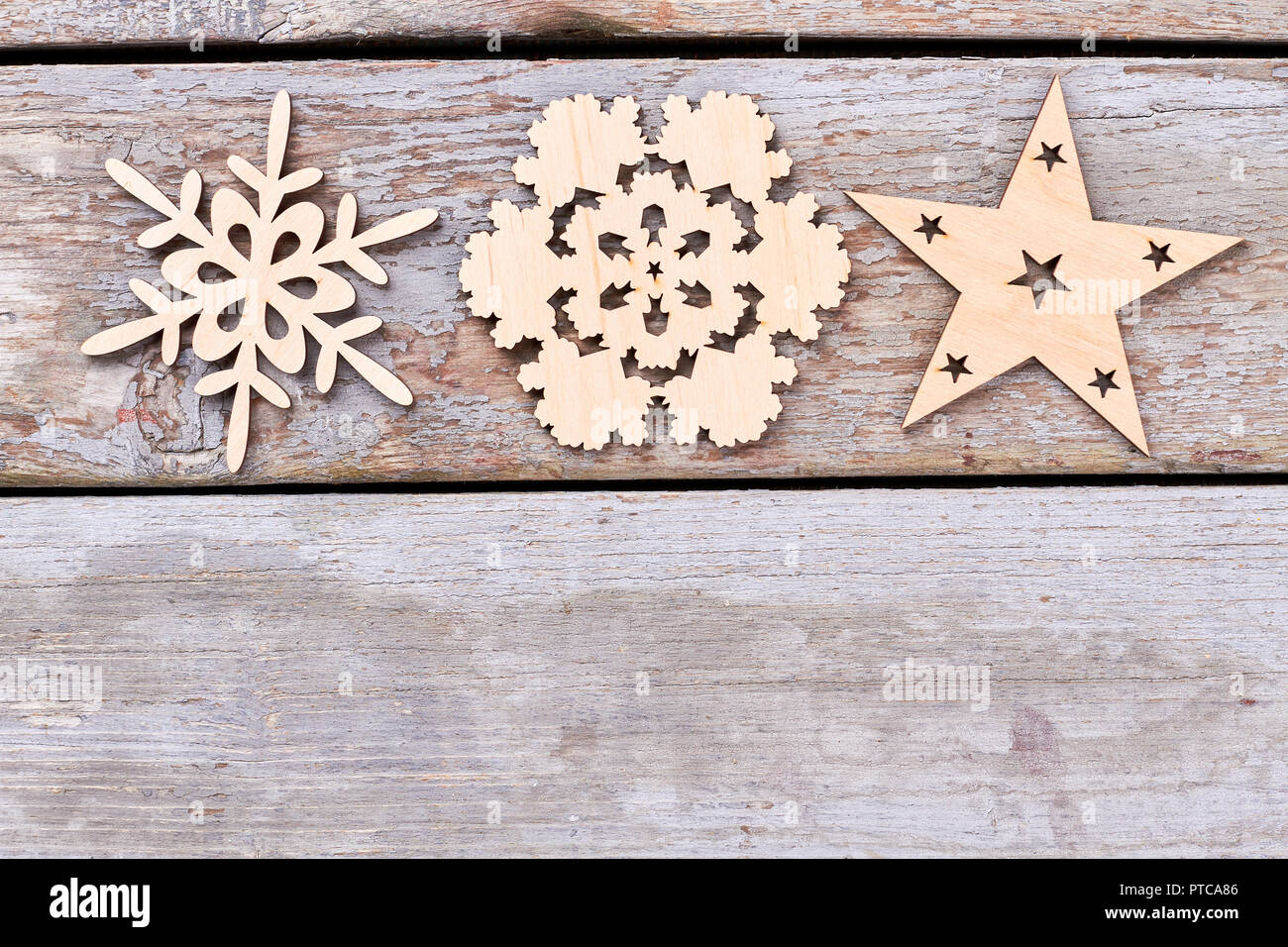 cut out wooden christmas decoration figures carved wooden snowflakes and star on old rustic wooden background copy space
