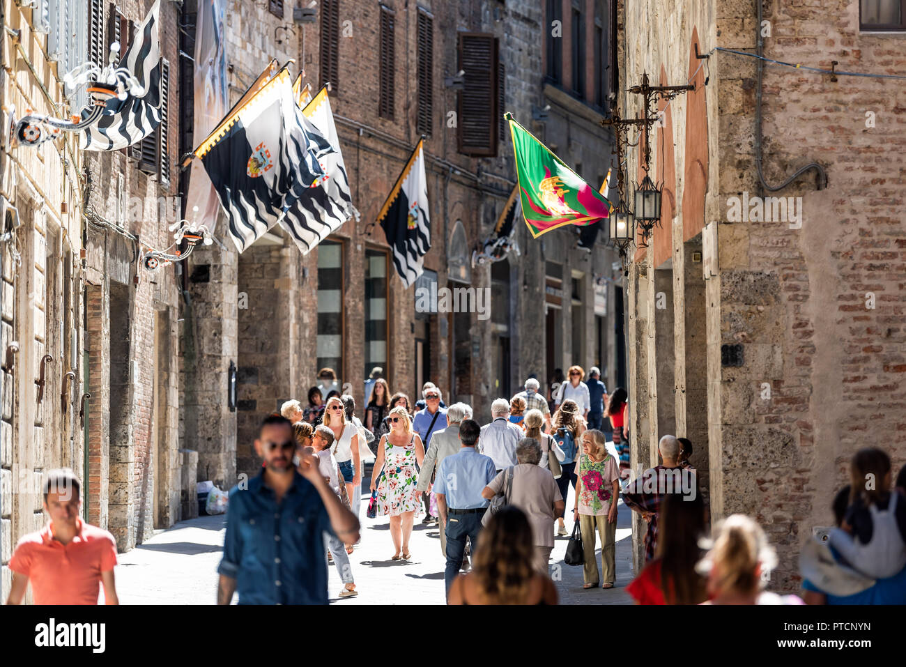 Siena, Italy - August 27, 2018: Street in historic medieval old town village in Tuscany with shopping stores, crowd of many people tourists walking, f Stock Photo
