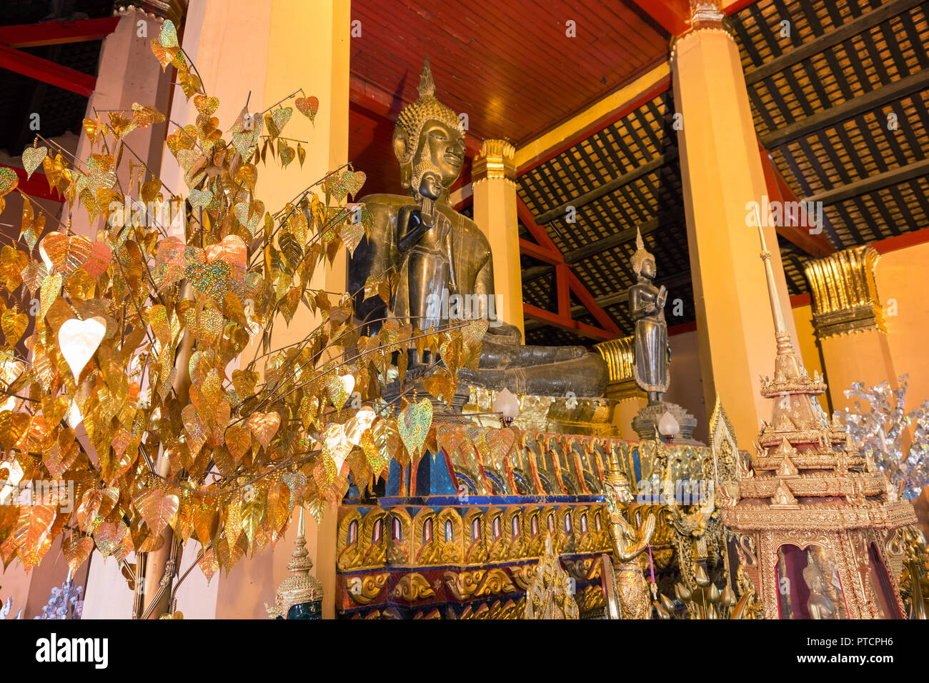 Altar with several golden Buddha statues and other items at the Wat Ong Teu Mahawihan (Temple of the Heavy Buddha), a Buddhist monastery, in Vientiane Stock Photo