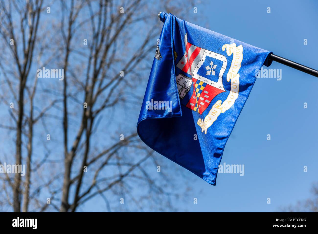Lexington, USA - April 18, 2018: Washington and Lee University flag in Virginia closeup isolated against blue sky with sign motto for Non incautus fut - Stock Image