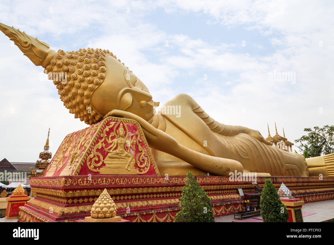 Large gilded Reclining Buddha statue at the Wat That Luang Tai Temple in Vientiane, Laos. - Stock Image