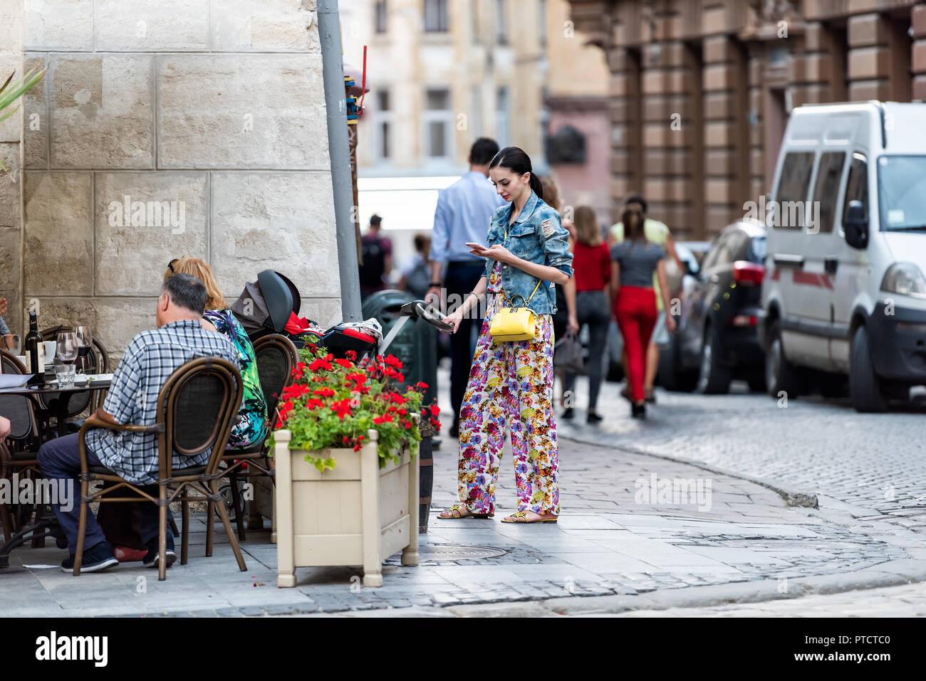 Lviv, Ukraine - July 30, 2018: Slavic Eastern European Ukrainian woman standing in historic Ukrainian Polish city in old town cobblestone street, baby - Stock Image