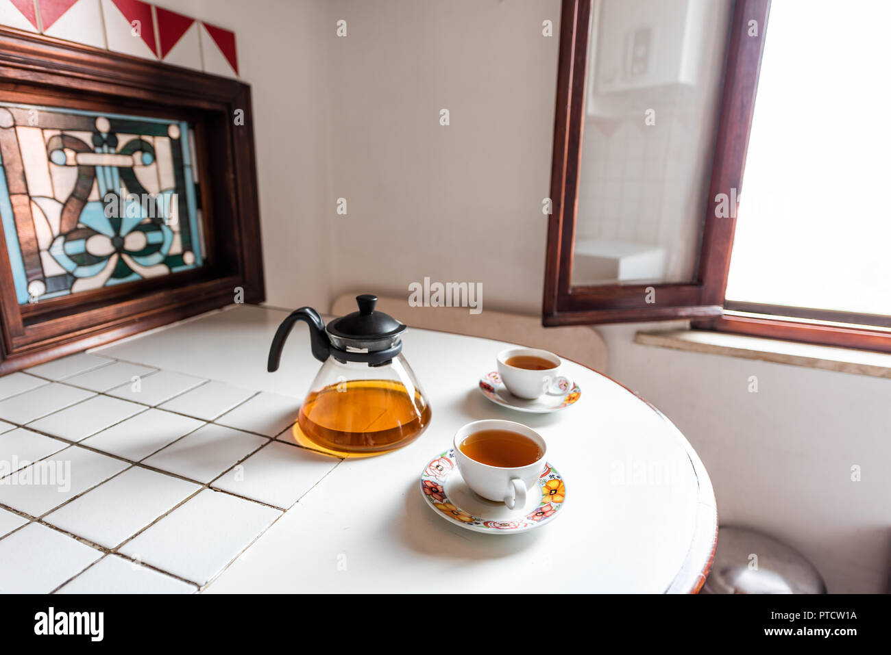 Two tea cups with black or green oolong tea herbal tea on white table with teapot pot in Italian villa rustic Tuscany home kitchen, sunlight Stock Photo