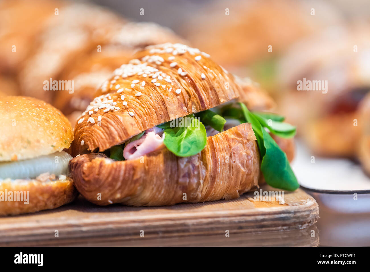 Closeup of savory breakfast croissant sandwich golden dessert in bakery, shop, cafe, store display tray with ham, arugula greens - Stock Image