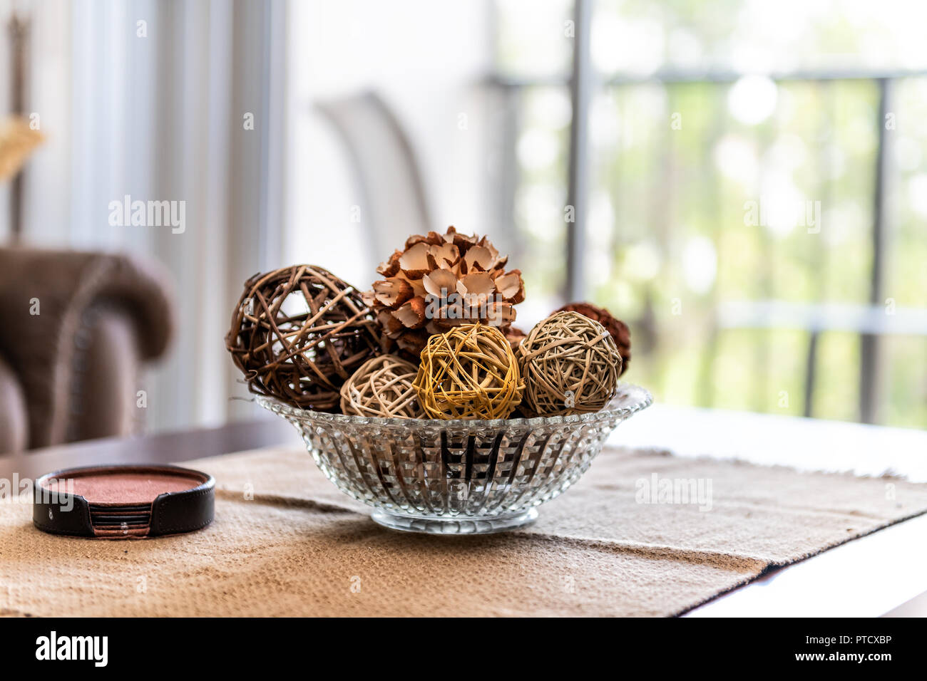 Modern, contemporary, clean decor with vase on table, tablecloths, coaster set, wicker balls and cone in apartment, home, house with bright light from - Stock Image