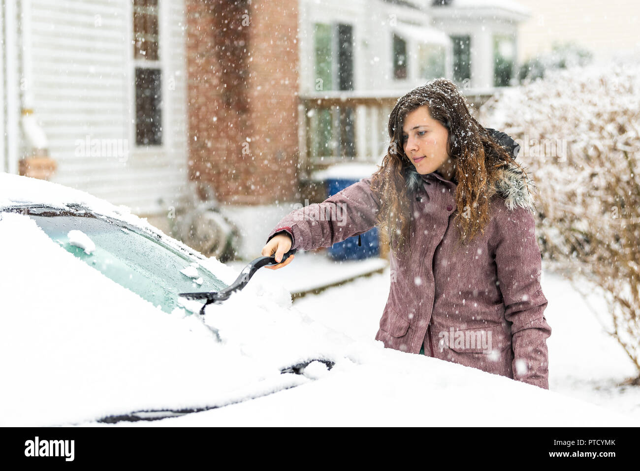 One young woman cleaning car windshield window from snow, ice with brush and scraper tool during snowfall while snowing snowflakes falling - Stock Image