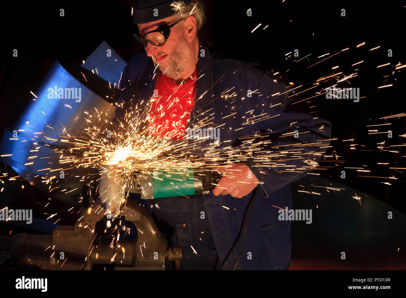A man, craftsman works with an angle grinder, flex, flying sparks, Germany - Stock Image