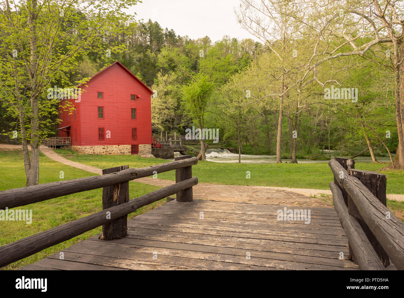 Red Mill Barn at the end of a wooden bridge, old grist mill, farm community Stock Photo