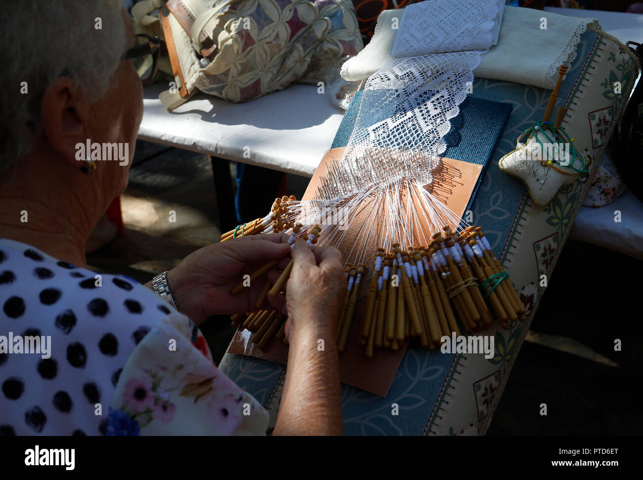 Bobbin lace weaver woman showing her traditional handmade technique during a local fair in the village of Esporles in the Spanish island of Mallorca. - Stock Image
